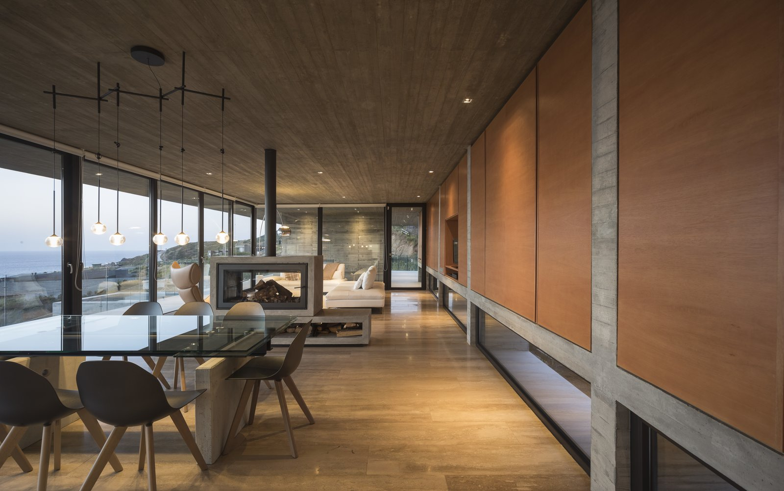 Dining Room, Recessed Lighting, Chair, Two-Sided Fireplace, and Table The living room, dining area, and kitchen have been designed as a single space within the main level.     Photo 6 of 14 in This Chilean Concrete Home Levitates Off a Coastal Slope