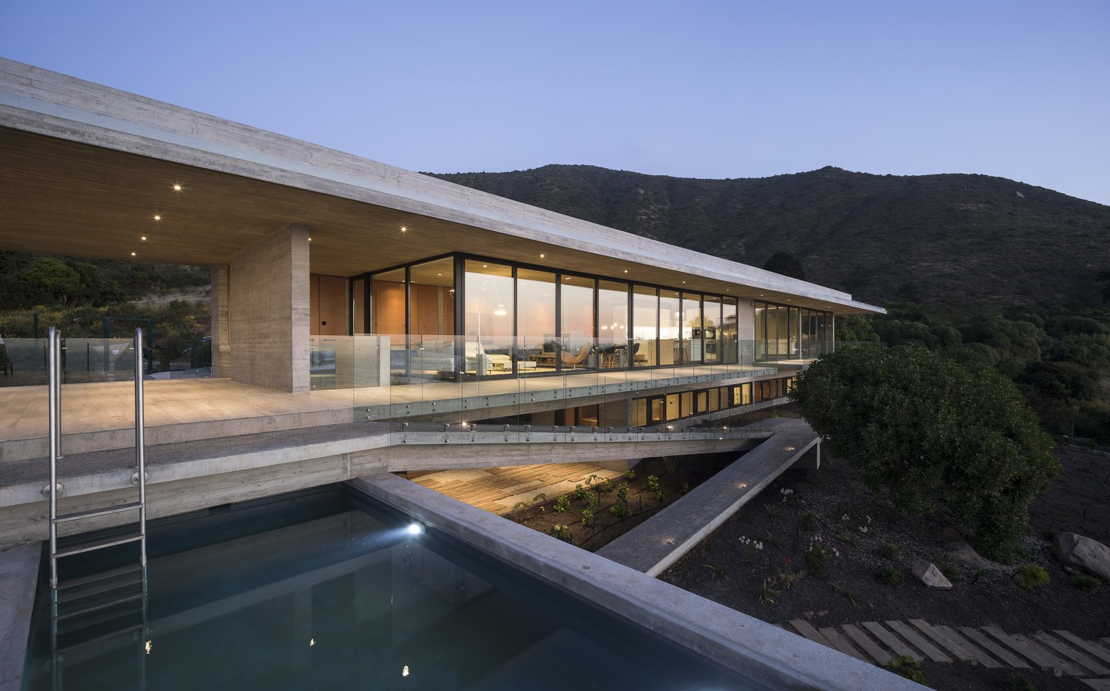 Outdoor, Small Pools, Tubs, Shower, Side Yard, Large Patio, Porch, Deck, and Concrete Patio, Porch, Deck The staircase and ramp serve as vertical circulation, connecting the base and access levels.     Photo 11 of 14 in This Chilean Concrete Home Levitates Off a Coastal Slope