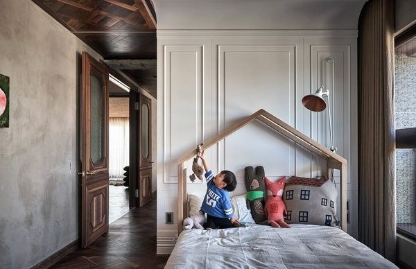 In the two bedrooms, the floors transition from polished concrete to warm parquet with interesting grains and varied shades, set in a latticed pattern.