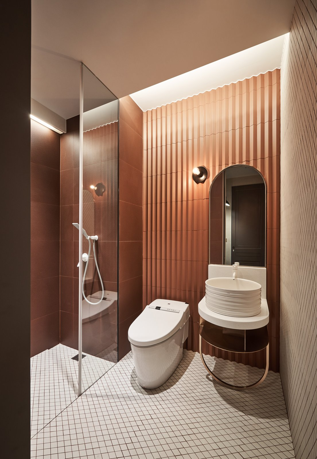 Bath Room, Porcelain Tile Floor, Vessel Sink, Open Shower, Wall Lighting, One Piece Toilet, and Corner Shower A deep vessel sink sits peacefully in this copper-hued bathroom.   Photo 14 of 25 in 25 Best Modern Bathroom Vanities For Your Home from Vintage and Industrial Elements Combine in an Updated Taiwan Apartment
