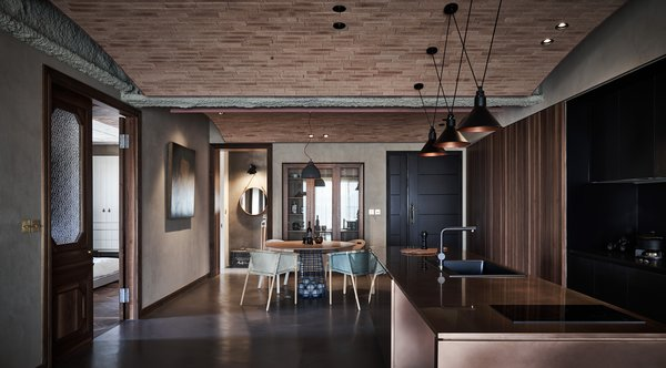 Within the open plan living-dining-kitchen space, they created a second ceiling in the form of three brick arcs that extend from one girder to the next, with each gentle arc rising over one of the functional zones.