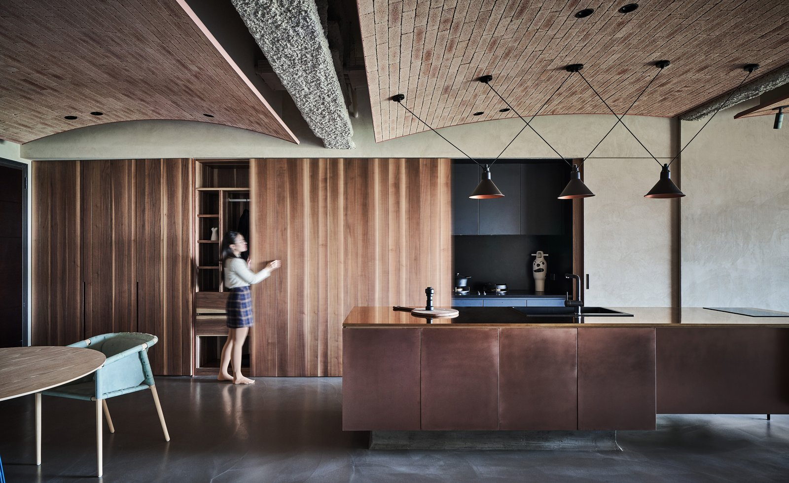 Kitchen, Metal Counter, Wood Cabinet, Pendant Lighting, Concrete Floor, Metal Cabinet, Drop In Sink, Recessed Lighting, and Cooktops A Taiwanese expat couple purchased a 1,352-square-foot apartment near the river in the Taiwan's New Taipei City, and reached out to interior design firm KC Design Studio to help them turn it into a stylish, modern home. Industrial elements like steel, brick, and exposed concrete harmonize with vintage accents: in the open kitchen, wood-paneled sliding doors conceal dark cabinetry. These combine with a sleek, dark counter and a shiny, bronze-clad island for a luxe effect.  Photo 1 of 15 in Vintage and Industrial Elements Combine in an Updated Taiwan Apartment