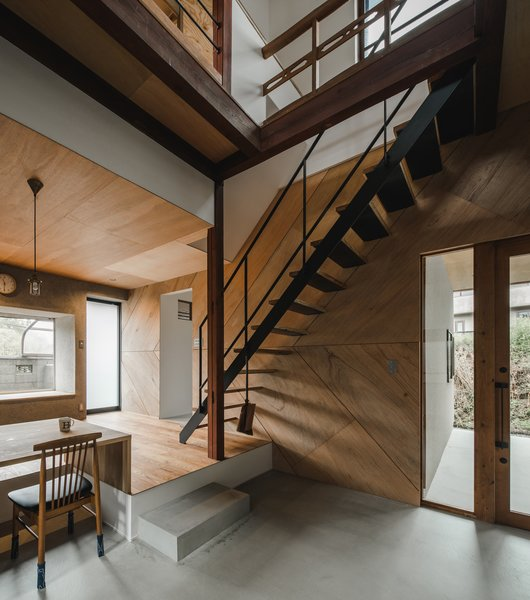 The architects installed modern, floating stairs with a wooden tread and steel railings.