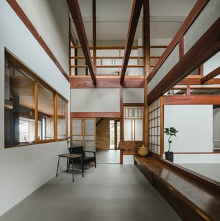 Elements from traditional Japanese architecture such as warm wood, exposed beams, and shoji screen-style sliding doors characterize the home.