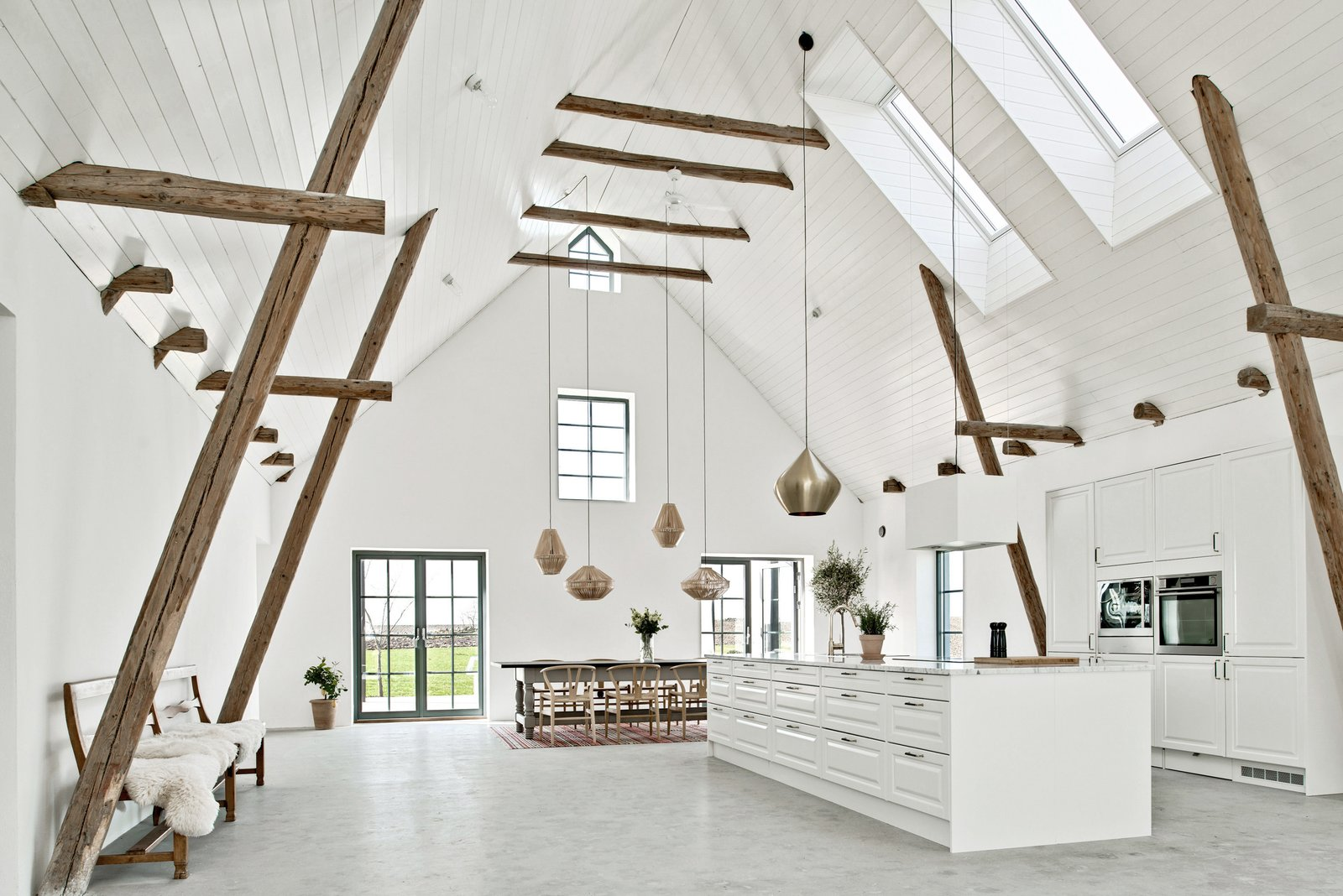 Kitchen, Concrete, Wall Oven, White, Pendant, and Marble The 4,198-square-foot home features rustic wooden beams that pay homage to the heritage of the buildings. These are set across the soaring 22-foot high ceilings.     Best Kitchen White Wall Oven Marble Pendant Photos from An Airy, Historic Home in Sweden Is Listed For Less Than $700K