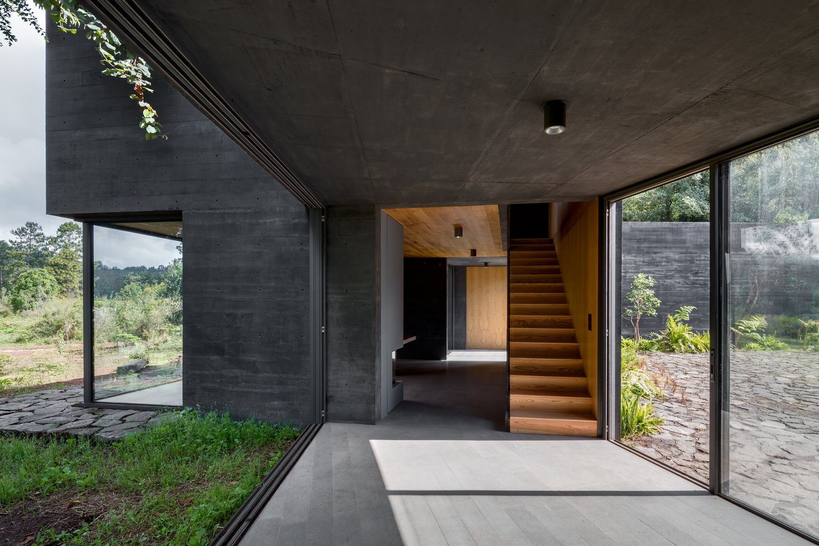Staircase and Wood Tread The design allows each volume to assert its independence while interacting with the other buildings in a rhythmic sequence.  Best Photos from Nine Black Concrete Volumes Form This Mexican Retreat