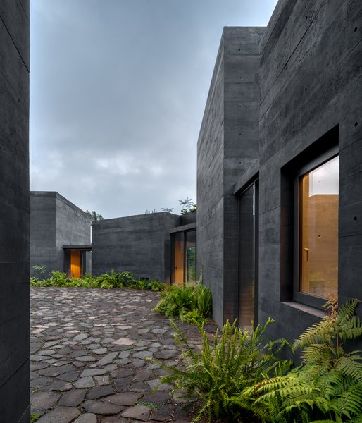 About 100 miles southwest of Mexico City, nine black concrete blocks in a forest clearing make up one family's holiday home. Designed by Mexican architect Fernanda Canales with landscaping by Claudia Rodríguez, Casa Bruma makes elegant use of a construction material that's commonplace in Latin America. The texture of the black board-formed concrete contrasts with the simple, rectilinear forms of the individual parts of the residence that surround a central patio paved with stone.