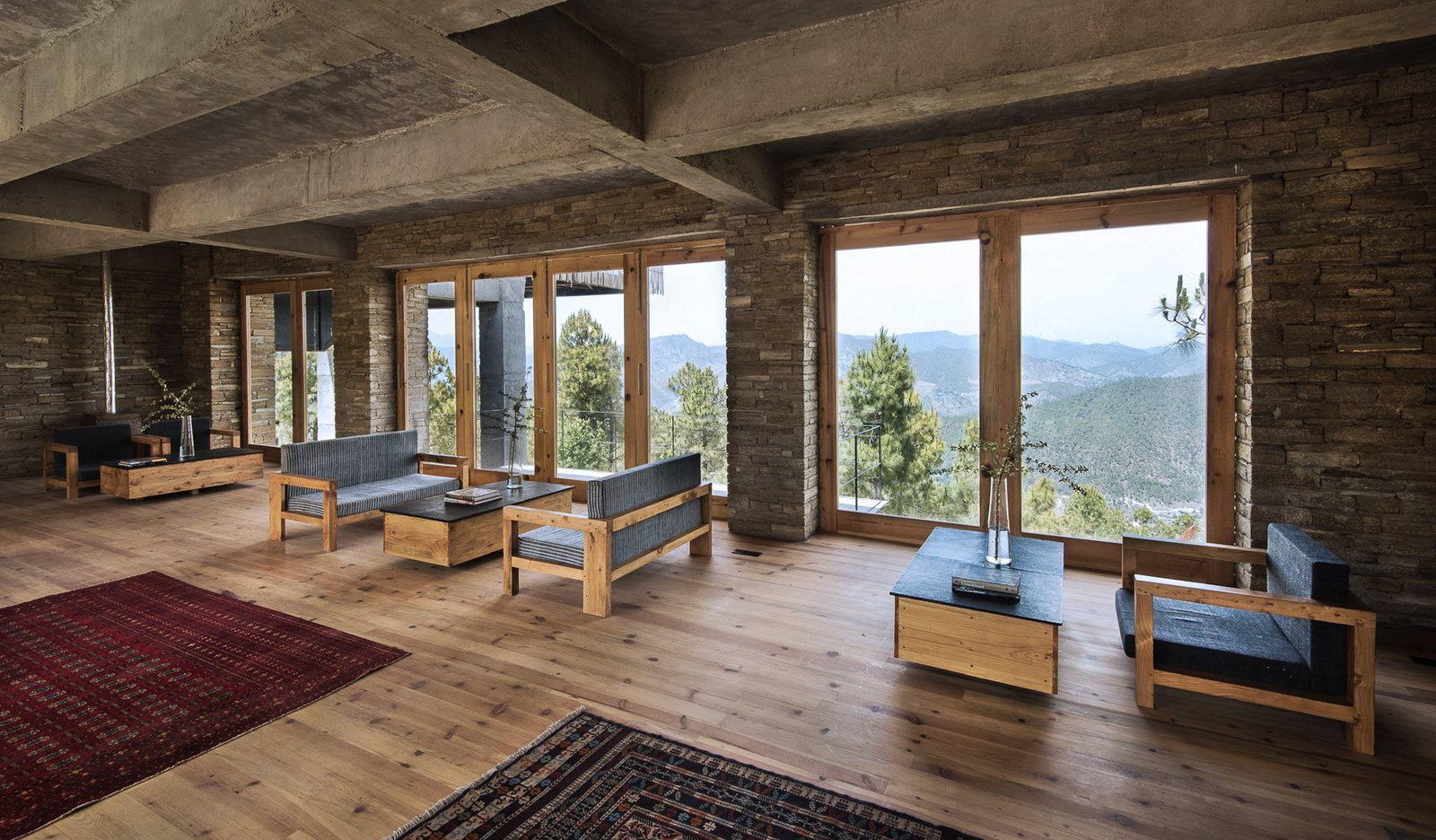 """Living Room, Coffee Tables, Medium Hardwood Floor, Sofa, and Rug Floor """"By dispersing the built structure around the site and using bamboo cladding, we were able to dissolve the visual impact a building such as this can have in a sensitive environment,"""" says Kodikara.  Photo 3 of 15 in A New Retreat in the Indian Himalayas Captures Epic Views"""