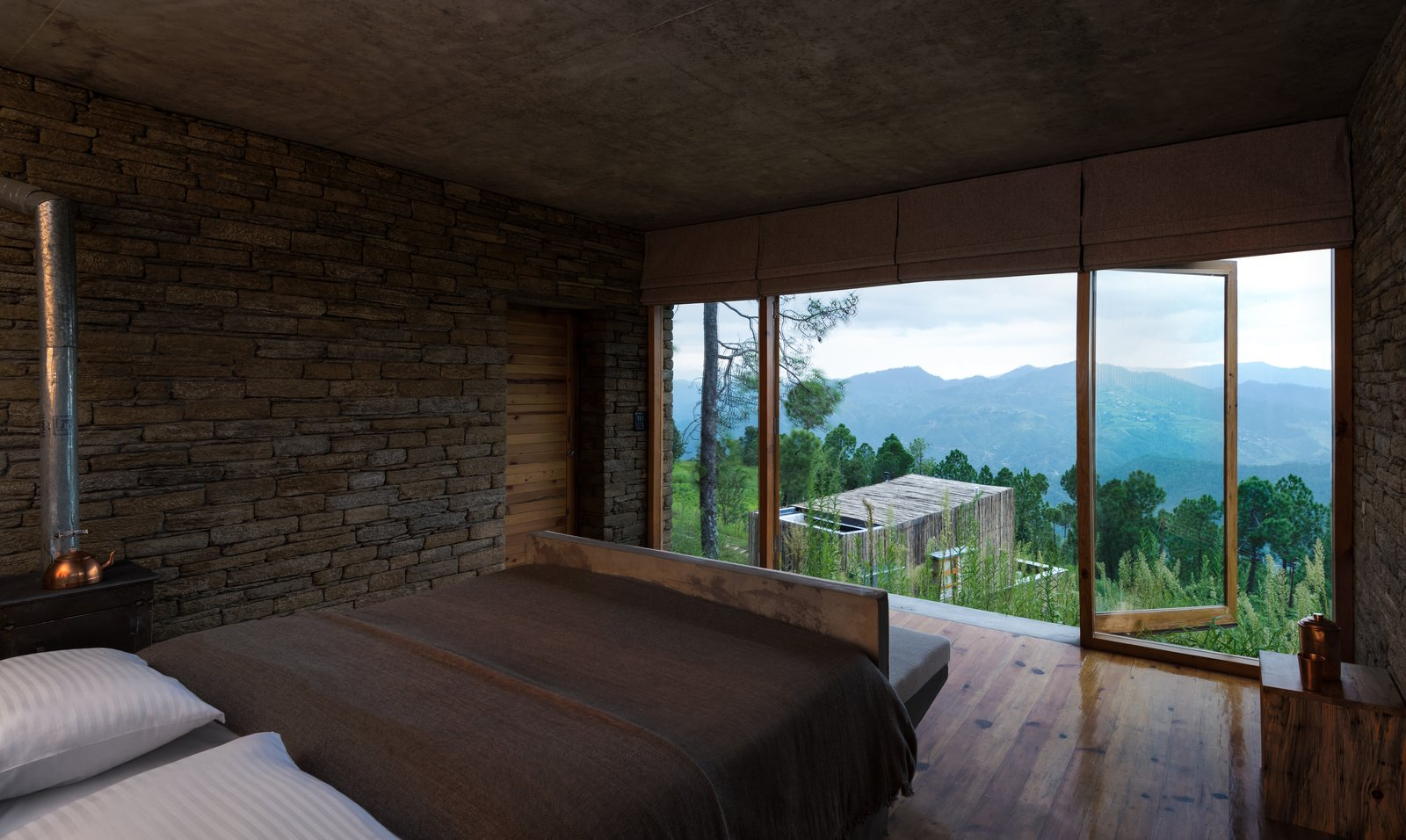 Bedroom, Bed, Medium Hardwood Floor, and Bench The guest rooms are located within chalet buildings that are scattered across the two-acre site, with each chalet split into two levels with one room on each.  Photo 9 of 15 in A New Retreat in the Indian Himalayas Captures Epic Views
