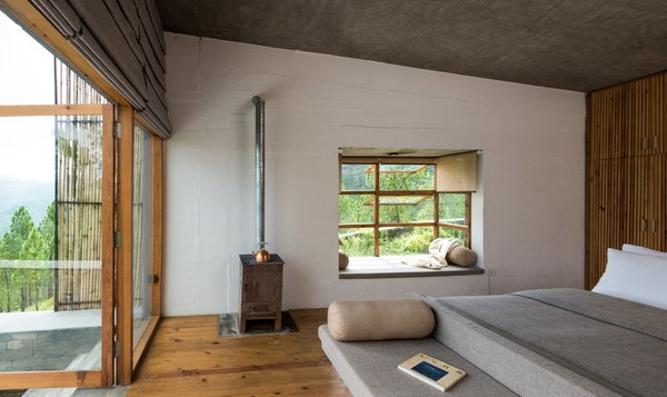In the chalet room, the bed, table, and seating were designed as a island unit finished in smooth cement render.