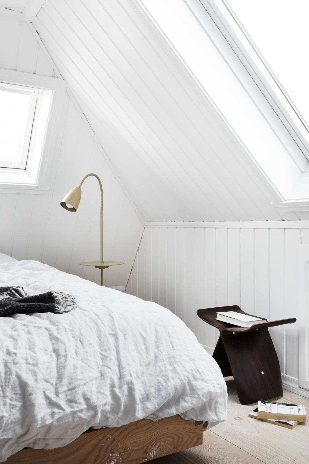 Bedroom, Bed, Chair, Light Hardwood Floor, and Floor Lighting To maximize the limited floor area, Saunders ripped down all the non-structural walls to open up the interiors, so the spaces feel roomier.  Photo 12 of 12 in An 18th-Century Townhouse Is Now a Chic Norwegian Rental