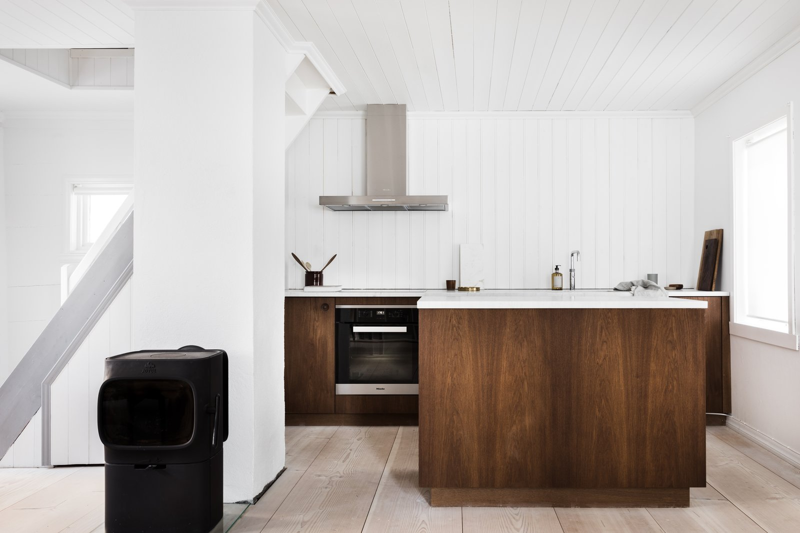 Kitchen, Light Hardwood Floor, Wood Backsplashe, Wood Cabinet, Wall Oven, and Range Hood The custom-designed kitchen worktops and cabinetry were hand crafted by Copenhagen furniture makers Møbelsnekkeriet.  Photo 4 of 12 in An 18th-Century Townhouse Is Now a Chic Norwegian Rental
