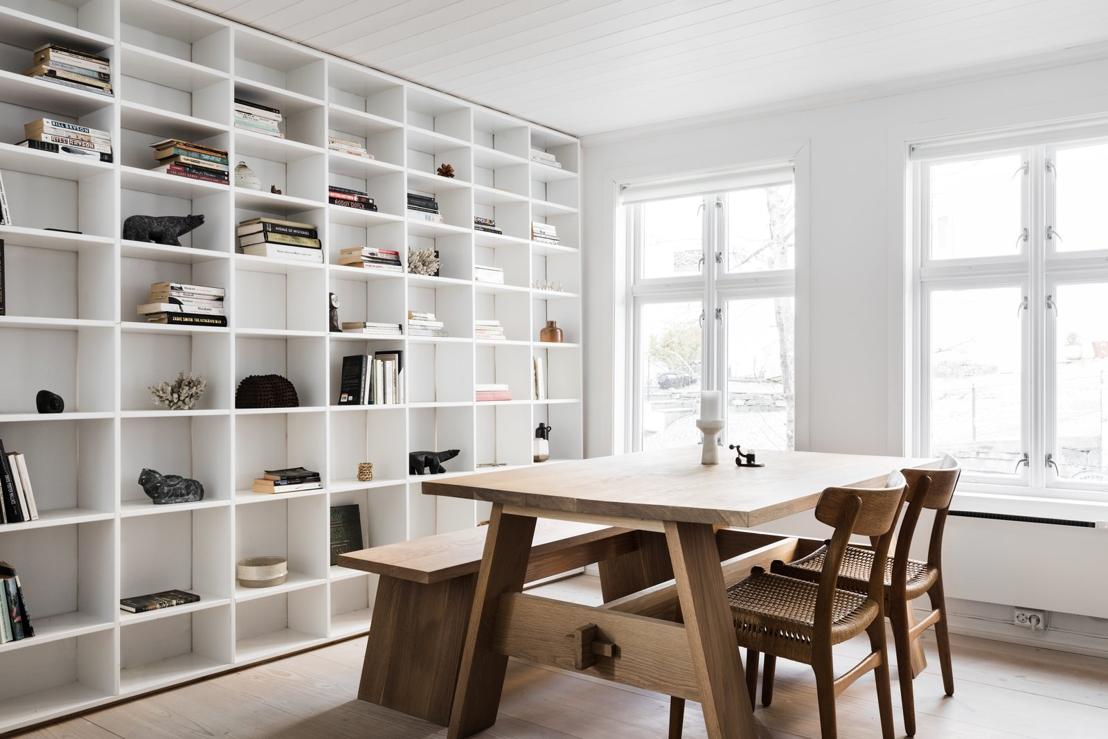 Dining Room, Table, Chair, Light Hardwood Floor, Bench, and Shelves Plenty of light pours in through the large windows in the main living area.  Photo 5 of 12 in An 18th-Century Townhouse Is Now a Chic Norwegian Rental