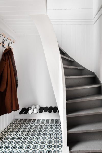 On the first floor, a tiled entrance foyer with storage space for a few jackets and about six pairs of shoes flows towards a master bedroom with a walk-in closet.