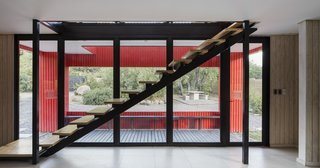 The interior staircase cuts diagonally across the floor-to-ceiling windows.