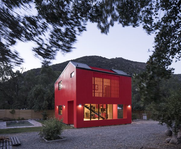 "This allowed Assadi to make a grand gesture by painting the two-level house bright red to complement the intense green of the surrounding trees, and to ""activate the relationship between the landscape and the project through contrast""."