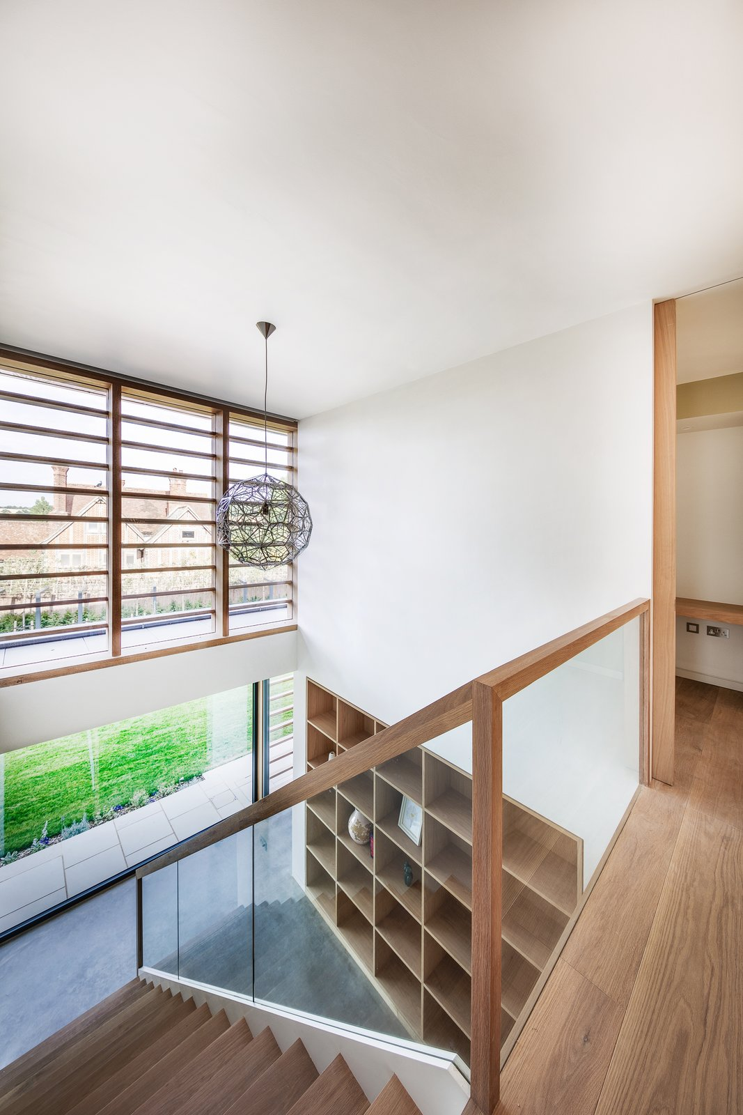 Staircase, Wood Tread, Wood Railing, and Glass Railing A glimpse at the Timber shutters from The New England Shutter Company.    Photo 11 of 17 in A 17th-Century Conservation Area in England Greets a Modern Home