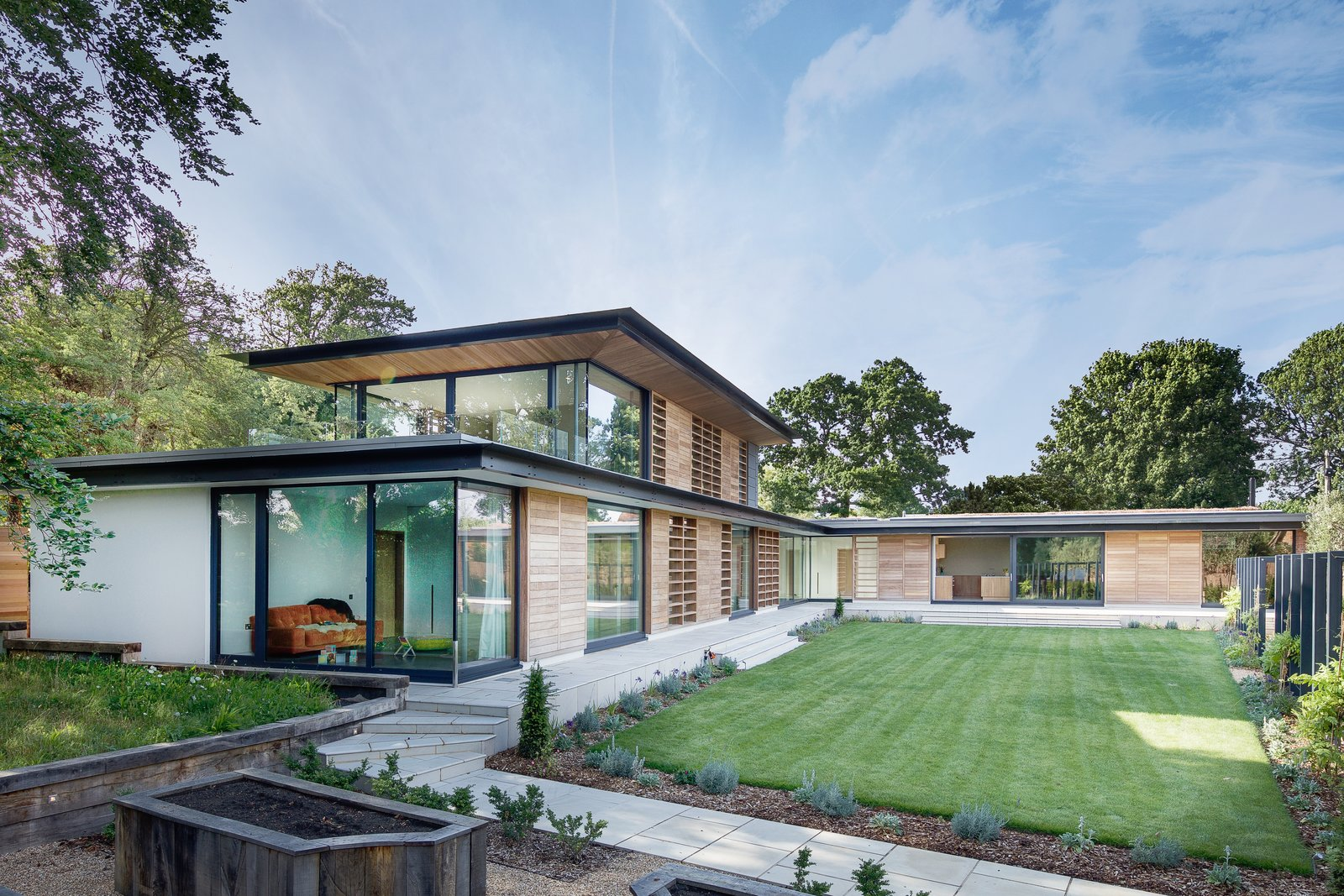 Outdoor, Walkways, Garden, Back Yard, Grass, and Gardens  An entrance hall, gallery, and double-height staircase connect the two wings, which frame views of the serene garden.      Photo 12 of 17 in A 17th-Century Conservation Area in England Greets a Modern Home