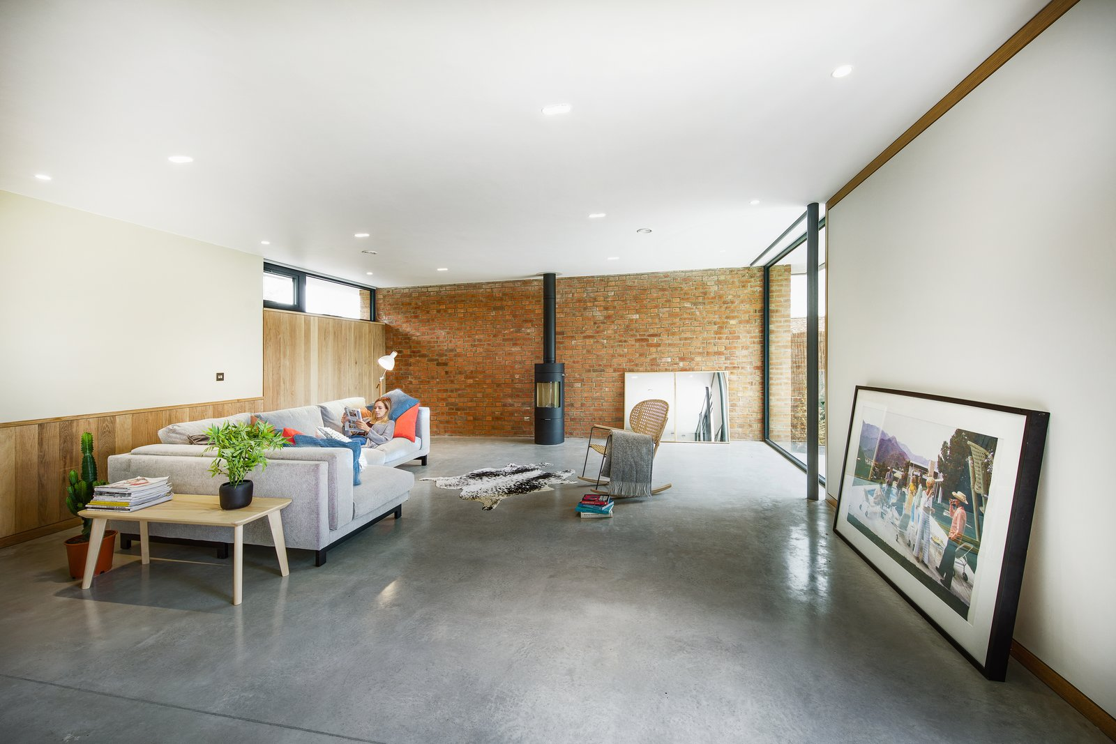 Living Room, End Tables, Sofa, Recessed Lighting, Concrete Floor, Floor Lighting, and Console Tables A solid brick enclosure has been used for the external north-facing wall.     Photo 6 of 17 in A 17th-Century Conservation Area in England Greets a Modern Home