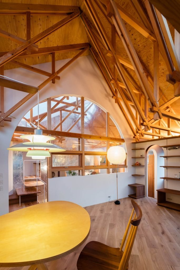 Living Room, Chair, Storage, Shelves, Table, Floor Lighting, Pendant Lighting, and Light Hardwood Floor This structure encloses the interior wall at an axis of 45 degrees on the plane.  Photo 9 of 17 in This Whimsical Home in Japan Encourages Play and Exploration