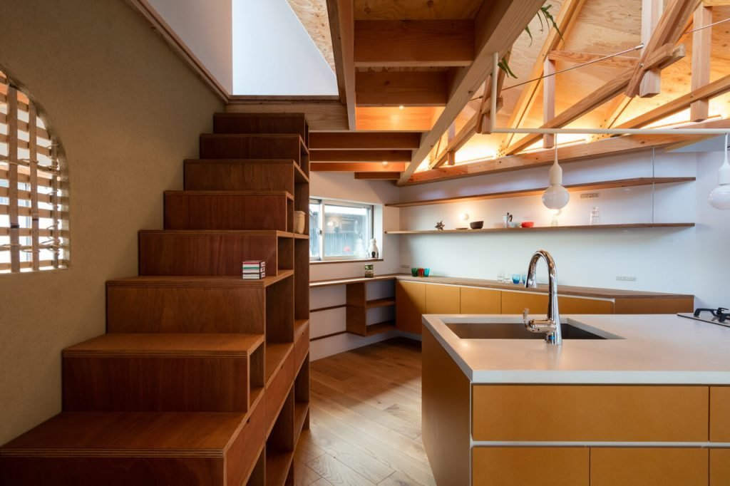Kitchen, Light Hardwood Floor, Pendant Lighting, Open Cabinet, Cooktops, and Undermount Sink On the second level is a large open plan living, dining and kitchen to the left of the stairs.  Photo 8 of 17 in This Whimsical Home in Japan Encourages Play and Exploration