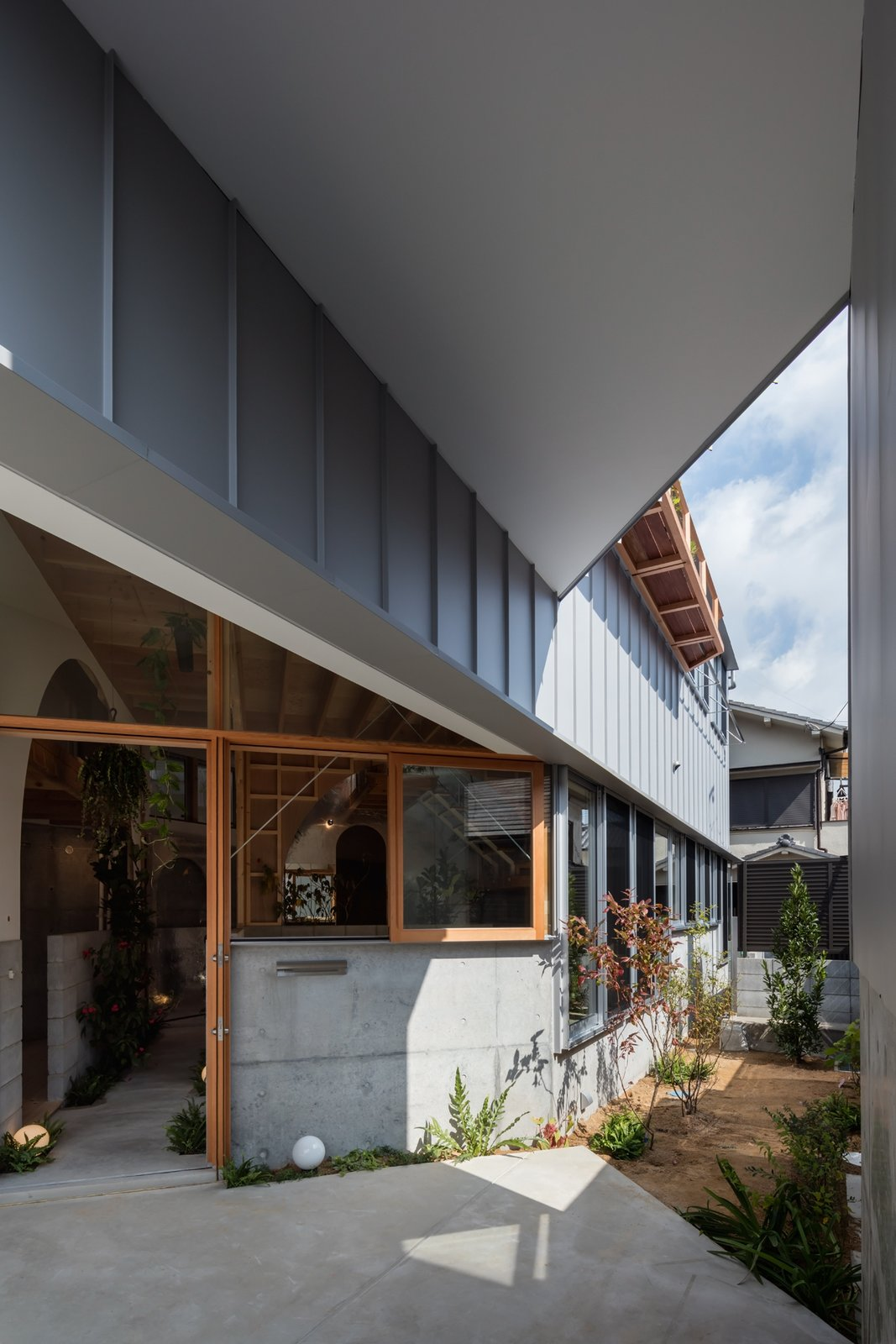 Doors, Exterior, and Wood The angle of the wall also enables the home to capture the ever shifting light entering from the southern side of the building.  Photo 4 of 17 in This Whimsical Home in Japan Encourages Play and Exploration