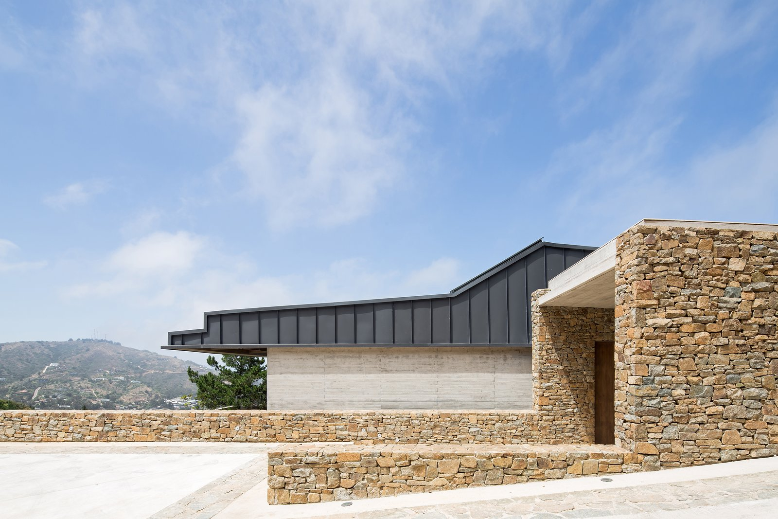 Garage This stone volume emerges from the topography like an ancestral cave, with its mouth serving as the entrance to the house.     Photo 2 of 14 in Two Eclectic Volumes Unite This  Contemporary Chilean Home
