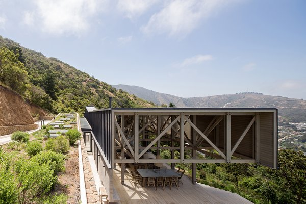 This volume has a rough hewn façade of stacked stones, and a green roof that seems to meld with the green hills of the surrounding El Boldo Park.