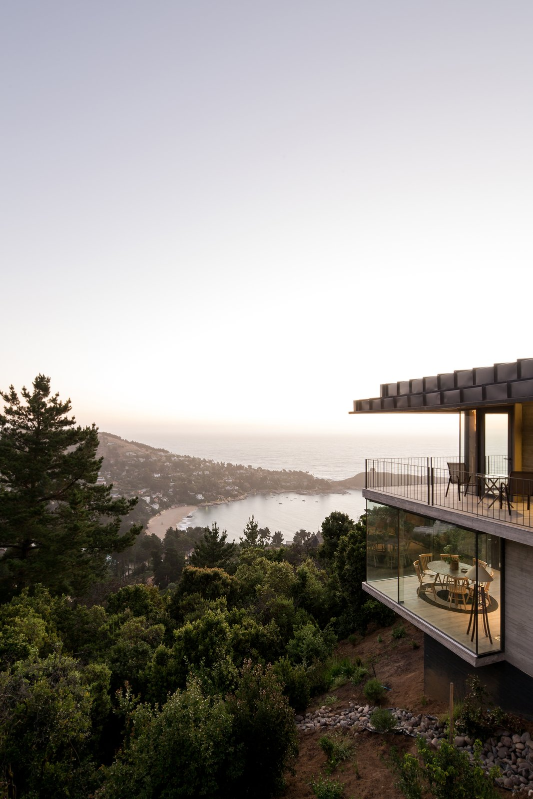 Exterior, House Building Type, Concrete Siding Material, Glass Siding Material, Flat RoofLine, and Green Roof Material A glimpse at the breathtaking views available from the home.    Photo 10 of 14 in Two Eclectic Volumes Unite This  Contemporary Chilean Home