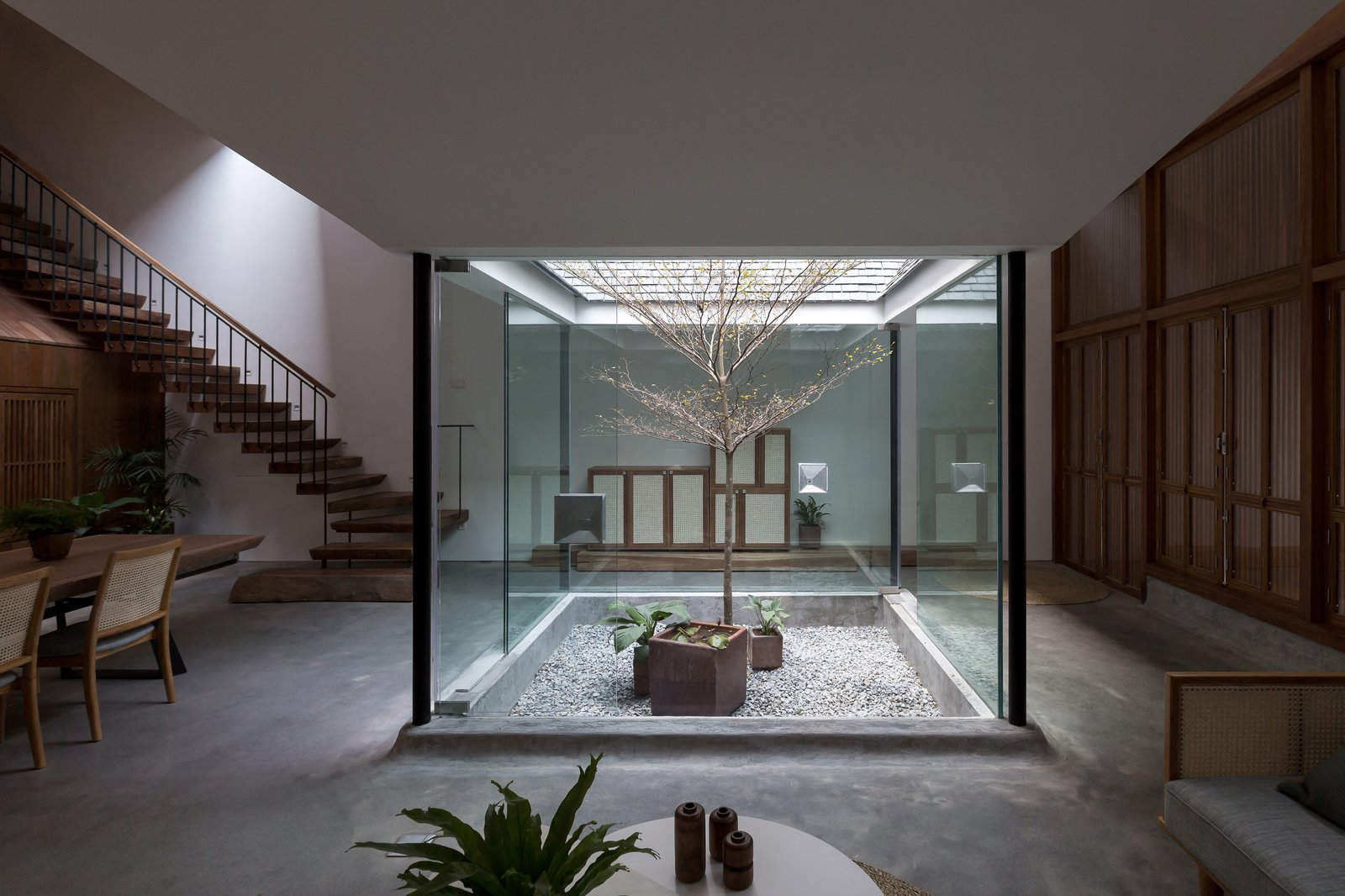 Outdoor, Gardens, Hardscapes, Raised Planters, Trees, and Garden Passing through a patio and entranceway, one enters an open-plan living and dining area with ceilings that dip towards the four glass walls of the small interior garden.  Photo 8 of 13 in A Vietnamese Abode Draws In Light With a Glass Atrium
