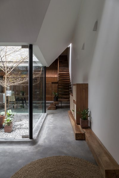 """From the living area, floating stairs lead up to the second and third floor, which were designed as two compact levels stacked above the """"wooden house"""" volume on the ground floor."""