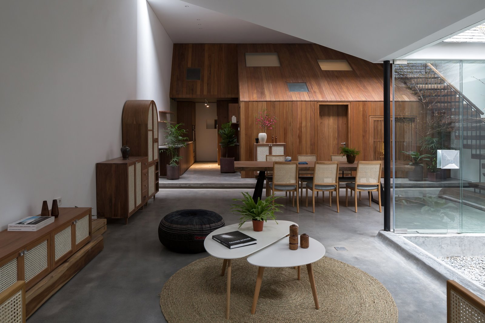 Living Room, Coffee Tables, Console Tables, Concrete Floor, Ottomans, and Rug Floor At the back of the living area is a volume shaped like a wooden house, which contains the kitchen, storage space, and a bedroom.   Photo 5 of 13 in A Vietnamese Abode Draws In Light With a Glass Atrium