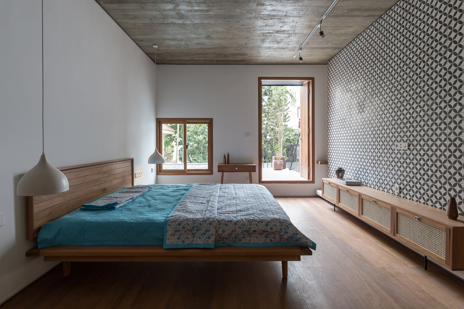 Bedroom, Medium Hardwood Floor, Storage, Pendant Lighting, Bed, and Track Lighting From these two balconies, one can look down at the top of the tree in the middle of the enclosed garden.  Photo 11 of 13 in A Vietnamese Abode Draws In Light With a Glass Atrium