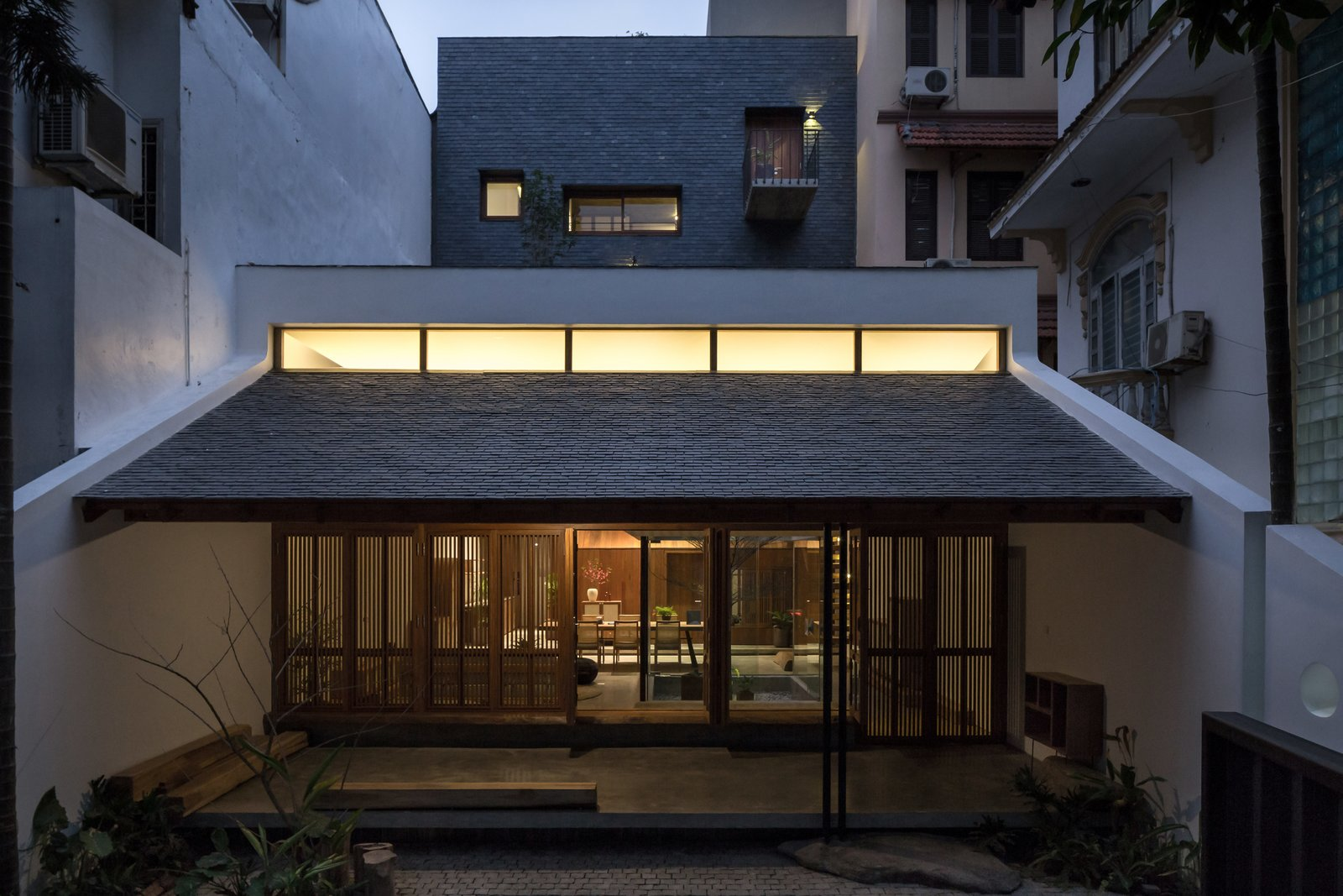 Outdoor, Large Patio, Porch, Deck, Front Yard, and Wood Fences, Wall All the decade-old trees within and around the existing house were retained.  Best Photos from A Vietnamese Abode Draws In Light With a Glass Atrium