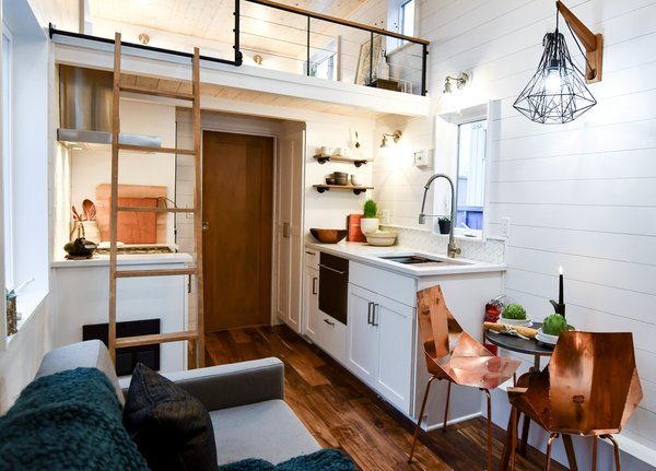 Beyond the living room is a kitchen with pullouts, closets, full-size tiny appliances, and a large Ruvatti sink.