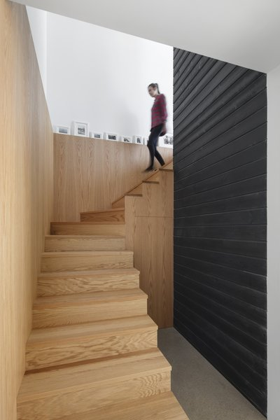 The walls of the living area are covered in horizontal black slatted wood, which gives the interiors of modern, Scandinavian feel.