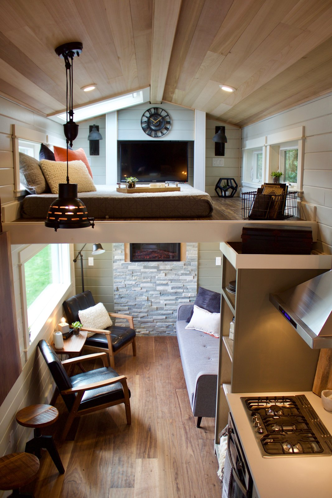 Bedroom, Bed, Pendant Lighting, Medium Hardwood Floor, and Ceiling Lighting The spacious living room features a fireplace and a remote-controlled, automated TV lift that slides upwards from the living room up to the master loft.   Photo 14 of 20 in This Oregon Company Crafts Exceptional Tiny Homes Starting at $40K