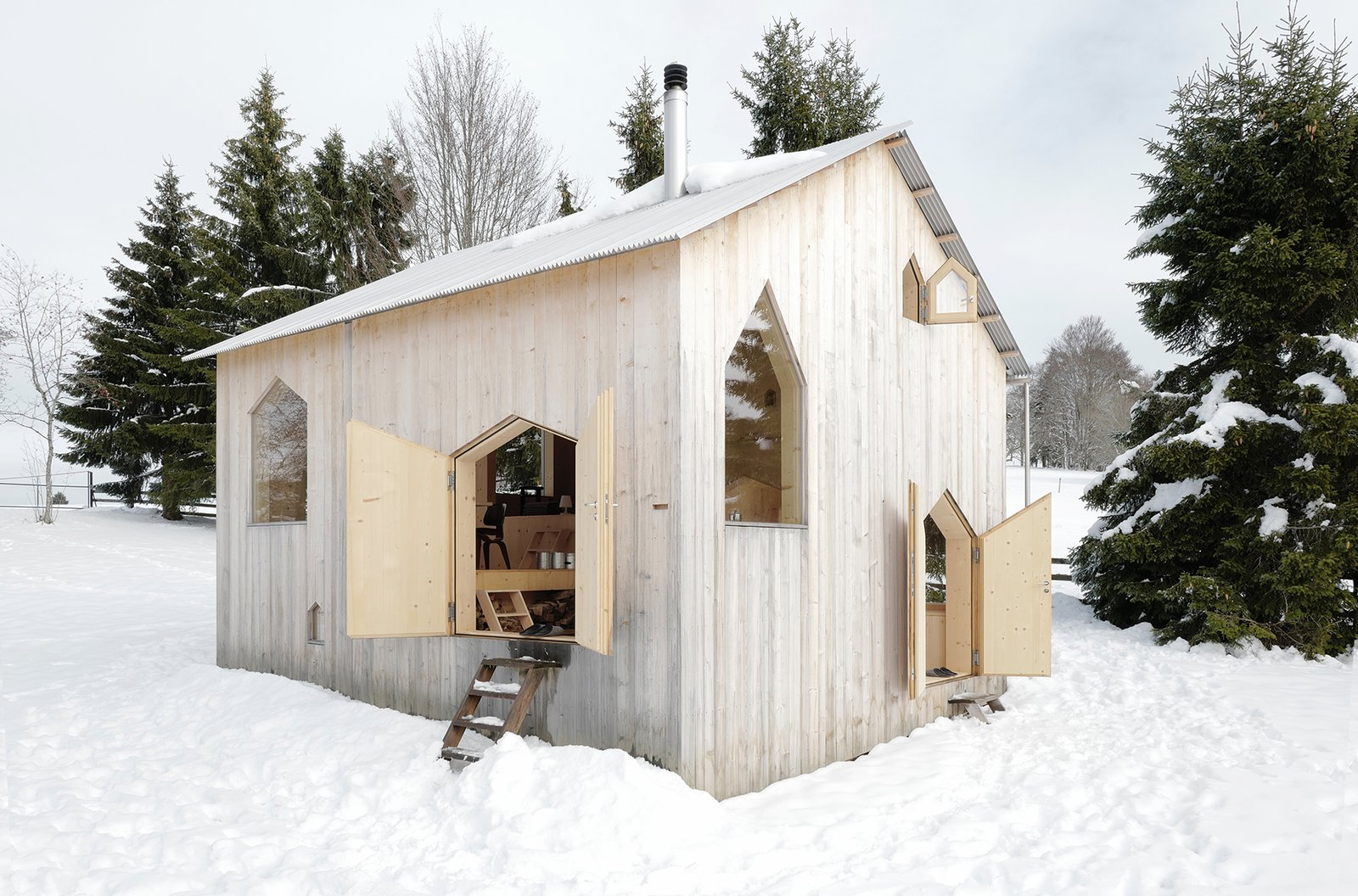Exterior, Wood, Cabin, Metal, Gable, and Small Home The roof is composed of a single sheet of folded stainless steel, and features a gutter on one side for rainwater harvesting.    Best Exterior Metal Wood Small Home Cabin Photos from An Outdated Swiss Chalet Is Treated to a Playful New Look