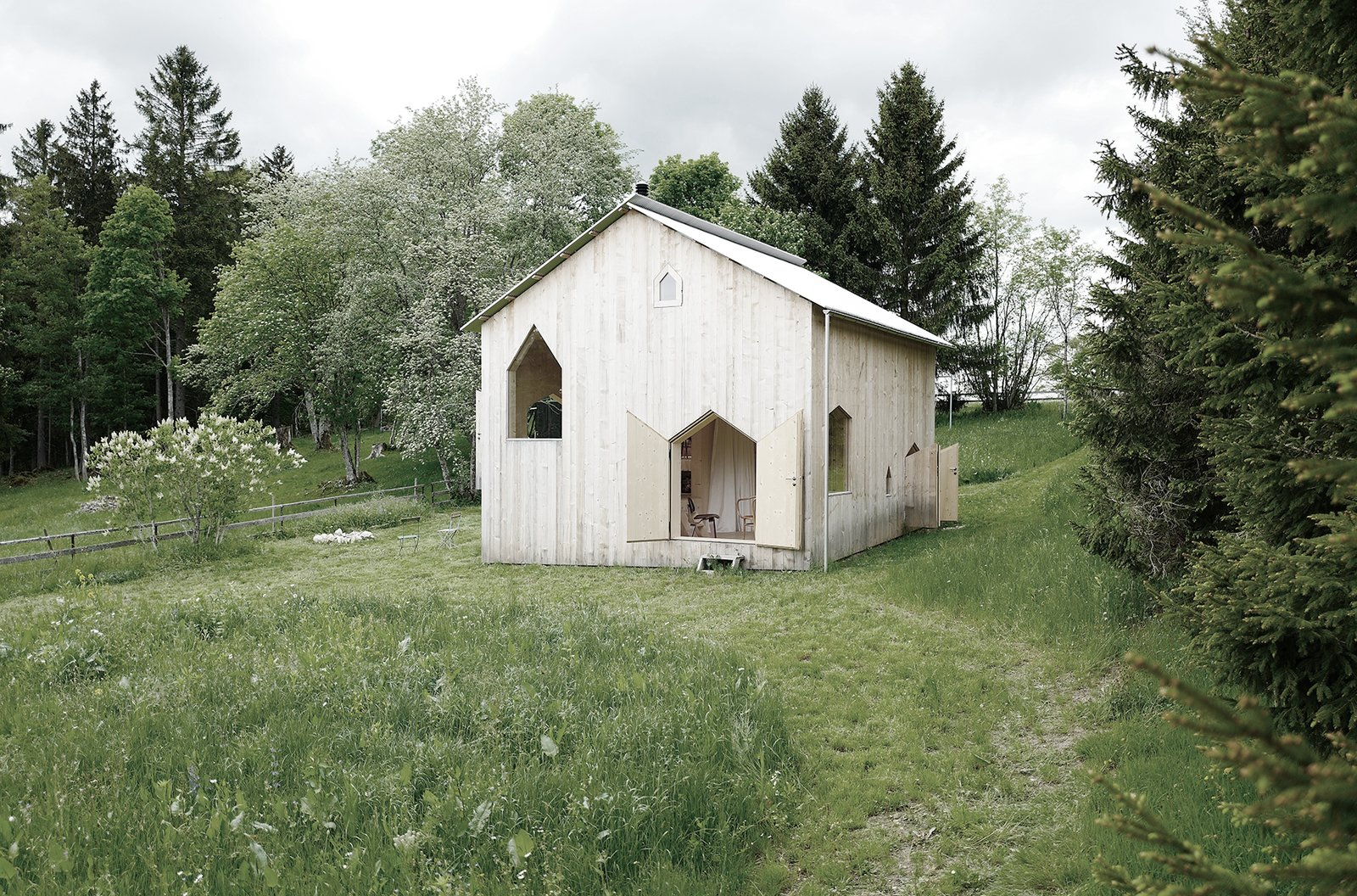 Exterior, Metal, Wood, Gable, Cabin, and Small Home Cut out of the walls at different heights, these doors reveal the unusual and quirky interior arrangement of the chalet.     Best Exterior Metal Wood Small Home Cabin Photos from An Outdated Swiss Chalet Is Treated to a Playful New Look