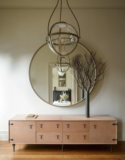 A BBDW leather credenza and round mirror, along with a chandelier by Urban Electric Kensington are located in the entry hall.