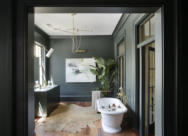 A Workstead brass chandelier, a Signal pendant, and an Urban Electric Rex table lamp have been used in the master bathroom.