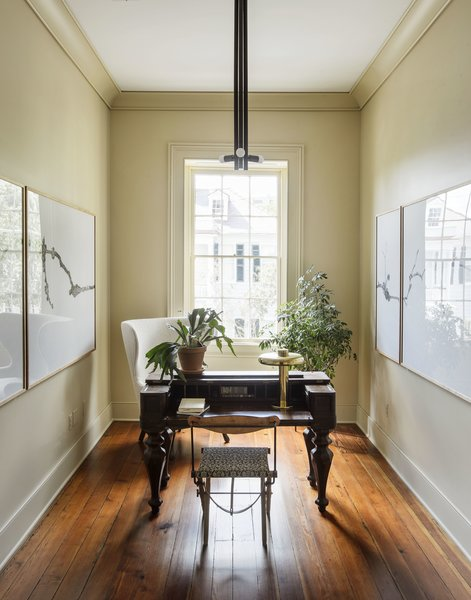 An antique desk, a Lawson Fenning Highland Wingback Chair, a Jim Bindman table lamp, a Workstead Lodge pendant, and art by Brandon Hinman can be found in the office.