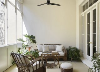 A vintage bamboo outdoor sofa, lounge chairs, and a coffee table sit together in the Veranda.