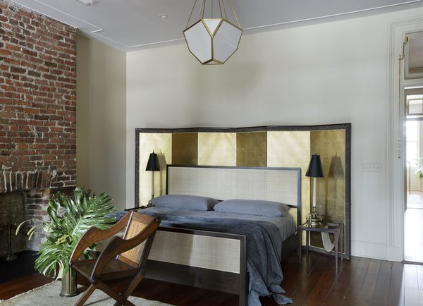 A Lawson Fenning cane bed, Selig night stands with fabric sling, an antique screen, and an antique barrel chair are in the master chambers.
