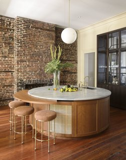 The house features a circular, marble-topped wet bar with Lawson Fenning Orsini stools.