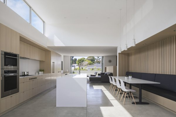 The built-in dining nook with dark gray banquette seating is textured with white oak vertical slats that reference the cement board fins on the house's façade.