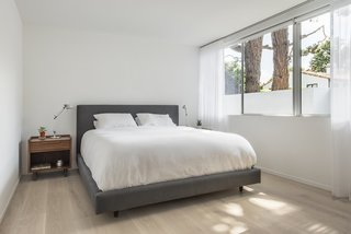 The simple and peaceful serene master bedroom looks out to the rear patio.