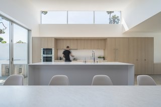 Clerestory windows bring plenty of natural light into the double-height kitchen. The kitchen has  a white quartz countertop and island, and a white Carrara marble tabletop.