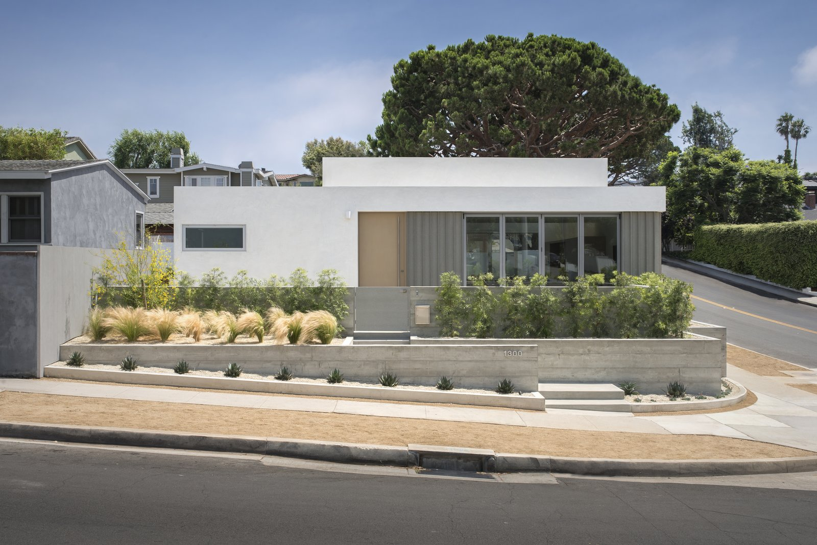 Exterior, Concrete Siding Material, House Building Type, Flat RoofLine, Metal Roof Material, and Mid-Century Building Type Sited on a cramped corner lot in Manhattan Beach, California, this midcentury bungalow was renovated and enlarged with a 1,000-square-foot addition to create a total of 1,986 square feet of functional space for owners Alison and Jeff Goad and their three children.   Culver City–based practice Edward Ogosta Architecture demolished and remodeled parts of the existing house to include a larger master bedroom and a new bedroom, bathroom, and powder room. The project also included updates to the two existing bedrooms, the laundry room, and garage.  Photo 1 of 15 in A Cramped Midcentury Bungalow Gets a Luminous New Addition