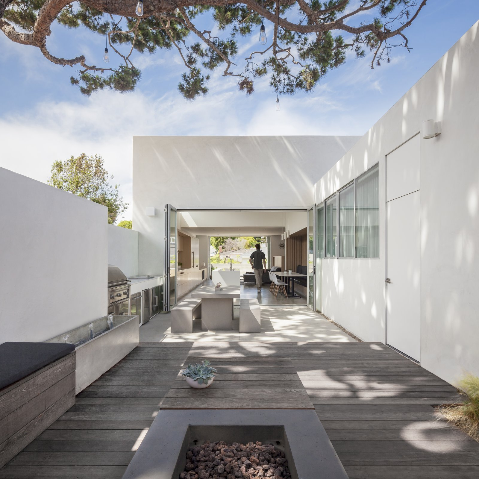 Outdoor, Trees, Wood Patio, Porch, Deck, Large Patio, Porch, Deck, Back Yard, Hanging Lighting, and Concrete Fences, Wall Edward Ogosta Architecture renovates and extends a Californian dwelling, creating a breezy, light-filled home for a family of five.   Best Photos from A Cramped Midcentury Bungalow Gets a Luminous New Addition